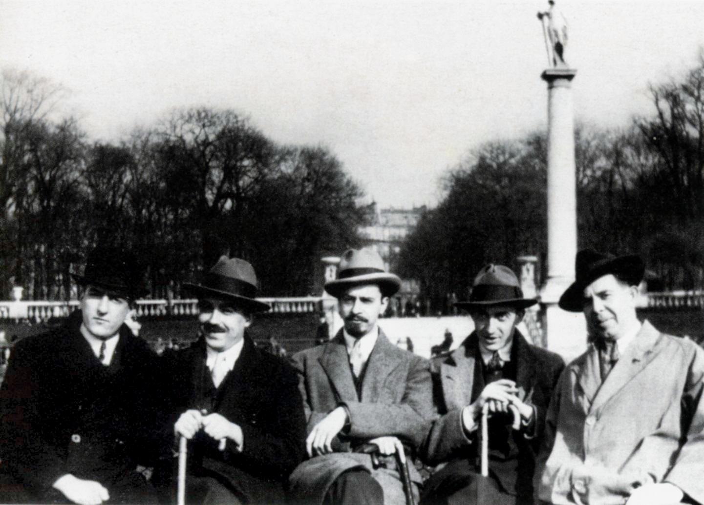 Φωτογραφία Στους κήπους του Λουξεμβούργου στο Παρίσι, το 1925. Από αριστερά: Γ. Κατσίμπαλης, Teriade, Ν. Χ. Γκίκας, Α. Κατακουζηνός και Μ. Τόμπρος. Συλλογή Γιώργου Γ. Κατσίμπαλη.